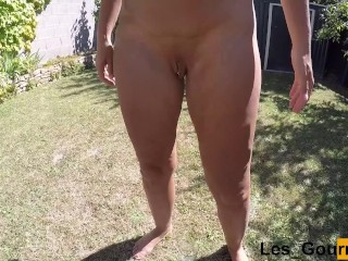 MILF tans naked outside and pissing in a tall glass