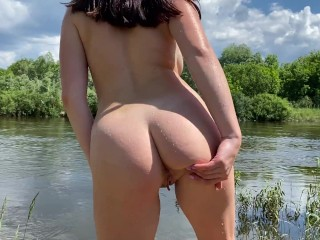 Russian doll bathing nude in countryside sea